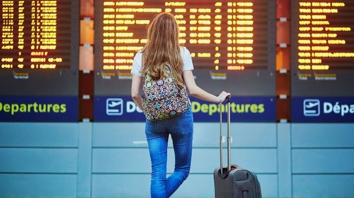 Woman at airport with backpack and carry on luggage